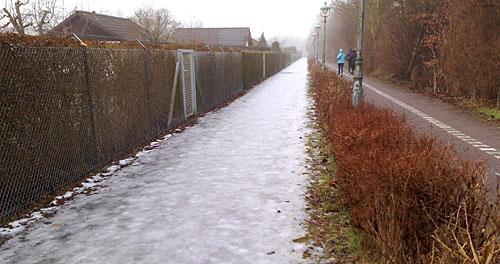 Läufer auf Radweg, neben vereistem Parkweg