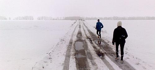 Läufer zwischen schneebedeckten Feldern