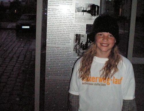 Die jüngste Läuferin vor der Mauer-Gedenktafel