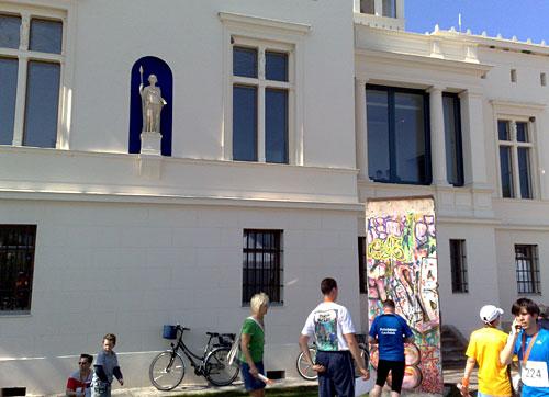 Gebäude mit Statue und Berliner Mauerstück