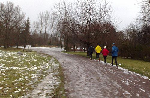 Läufer auf Parkweg mit Schneematsch