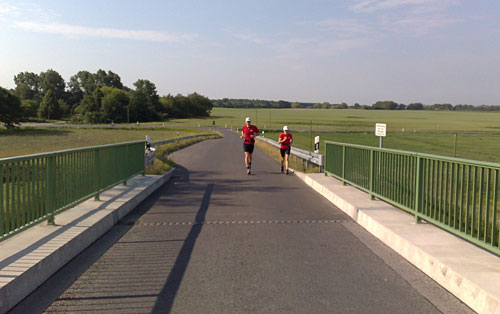 Läufer vor dem Brückenanstieg