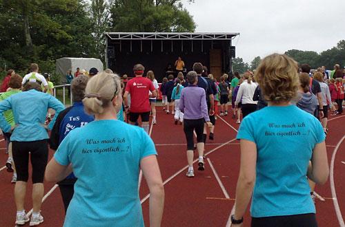 Läuferinnen und Läufer vor der Bühne beim Warm-up