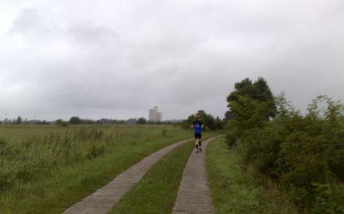Läufer auf Plattenweg zwischen Wiesen, am Horizont ein einsames Hochhaus