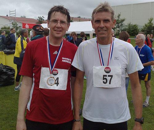 Zwei Läufer mit Medaillen im Ziel