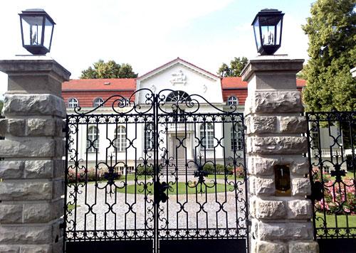 Prächtiges Eingangstor mit Villa im Hintergrund