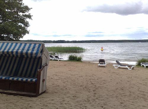 Strand mit Strandkorb und Blick auf den See