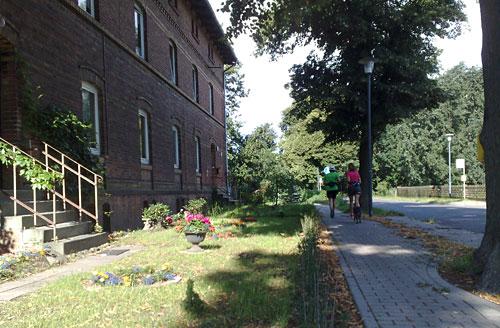 Läuferinnen auf Fußweg neben Backstein-Haus