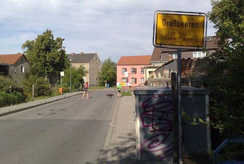 Ortsschild Großbeeren mit Läuferinnen im Hintergrund