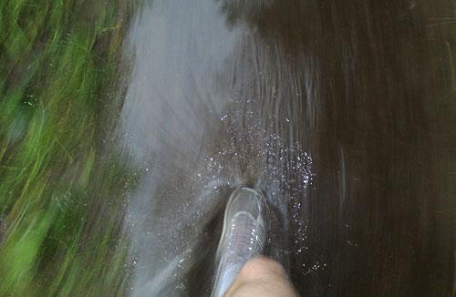 Läufer-Fuß beim Lauf durch eine Pfütze
