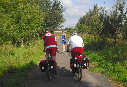 Läufer mit Sanitätern auf Fahrrädern