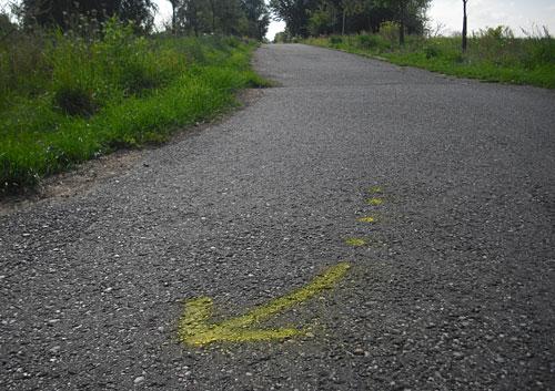 Bodenmarkierung: ein Pfeil zeigt Läufern den Weg