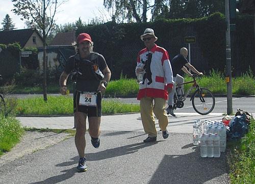 Läufer passiert die Getränkestelle in Marienfelde an der B101