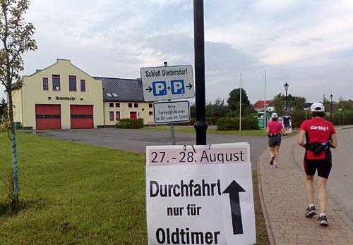 Läufer bei Feuerwache mit Schild Durchfahrt nur für Oldtimer