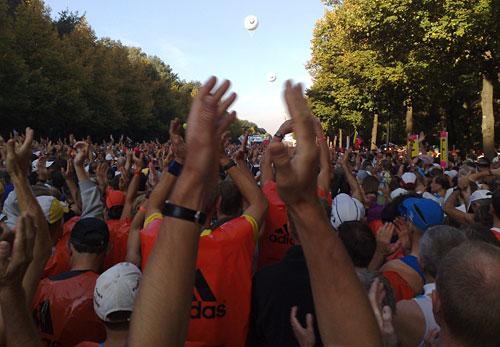 Läufer heben ihre Hände und klatschen im Takt