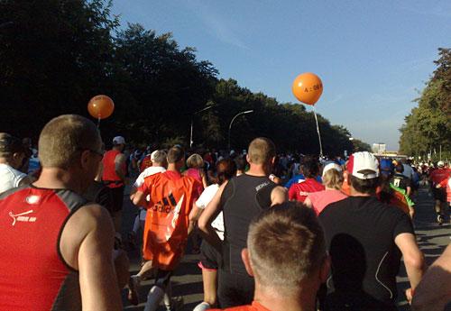 Läuferfeld über dem 2 orange Luftballons mit 4:00 schweben