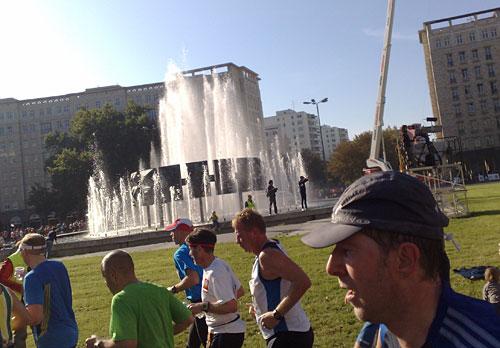 Marathon-Läufer und im Hintergrund Wasserspiele