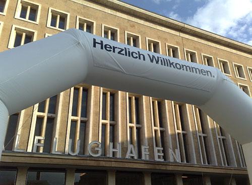 Aufblasbarer Torbogen mit Herzlich Willkommen vor dem Flughafengebäude