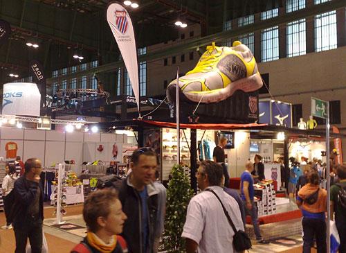 Riesengroßer Laufschuh über einem Messestand