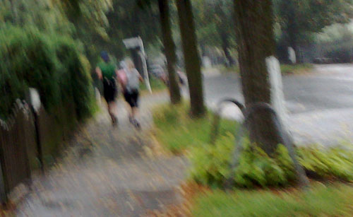 Läufer auf Fußweg im Regen