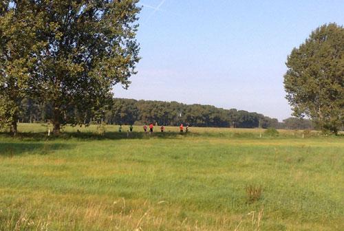 Läufer in grüner Landschaft vor blauem Himmel