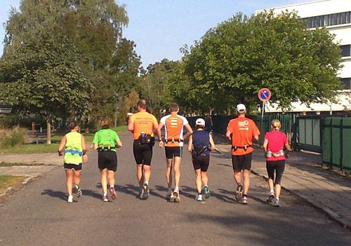 7 Läufer laufen nebeneinander auf einer Straße
