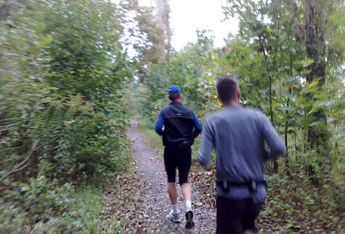 Zwei Läufer auf einem schmalen Pfad zwischen Büschen und Bäumen