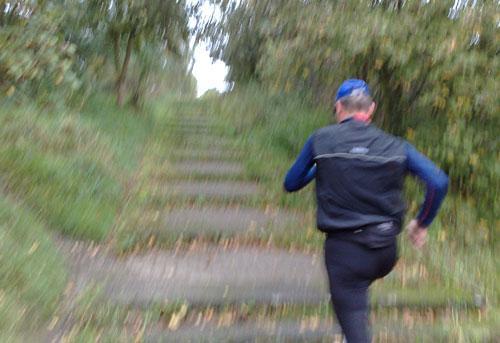 Läufer bei steilem Anstieg über einen Weg mit langgezogenen Treppen