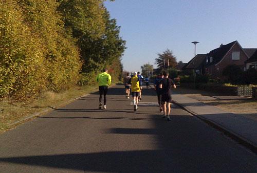 Läufer auf Asphaltstraße entlang von Einfamilienhäusern
