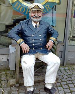 Seemann-Figur im Stuhl vor einem Geschäft