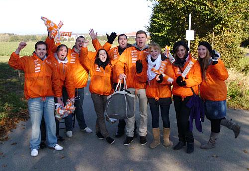 Gruppe von fröhlichen Lübeck-Marathon-Helfern in orangen Regenjacken