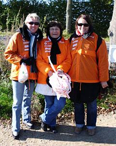 Drei freundliche Helferinnen in orangen Lübeck-Marathon-Regenjacken