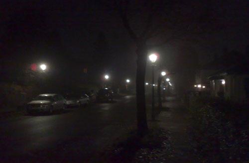 Einsame, neblige Straße in der Dunkelheit