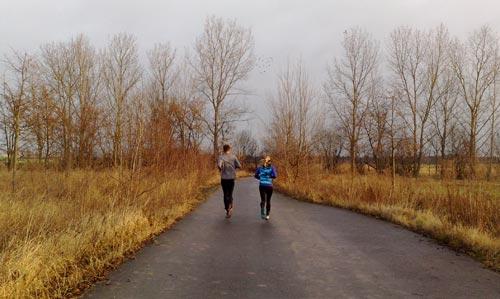Läuferin und Läufer auf Asphaltweg