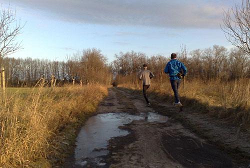 Läufer auf Weg mit zugefrorenen Pfützen