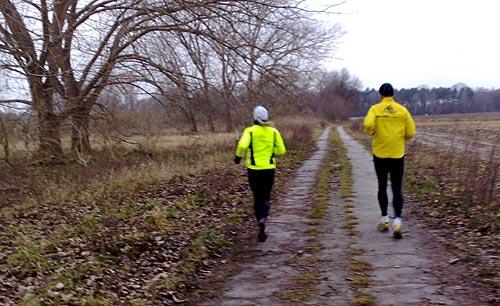Läuferin und Läufer mit gelben Jacken auf Weg
