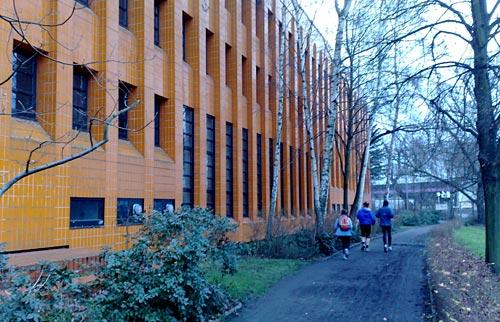 Läufer auf Weg neben einem orange-gekachelten Gebäude