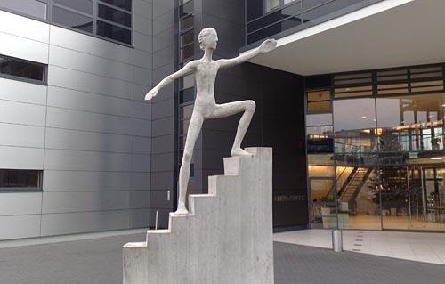 Skulptur eines Mannes auf einer Treppe
