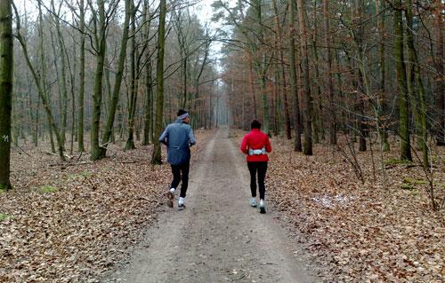 Läufer und Läuferin auf Waldweg