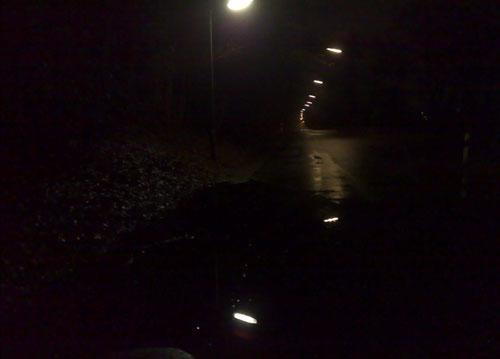 Dunkle Straße mit großer Pfütze