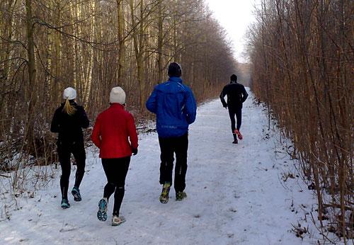 Läuferinnen und Läufer auf dem schneebedeckten Mauerweg