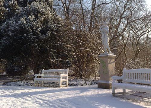 Statue und Bänke im schneebedeckten Gutspark Marienfelde