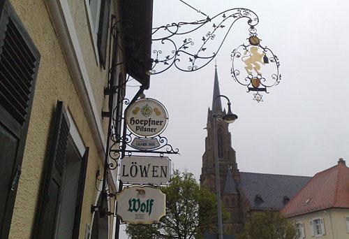 Gasthaus-Schilder und Kirche im Hintergrund