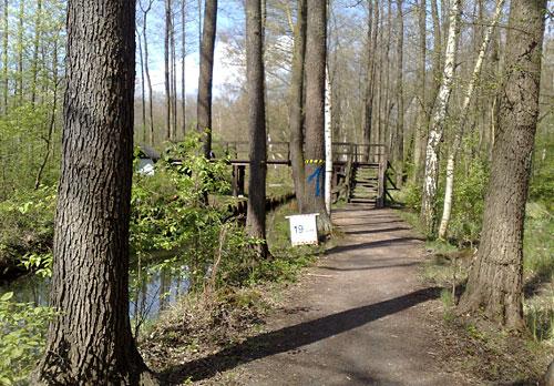 Kilometerschild 19 vor einer Holzbrücke über den Kanal