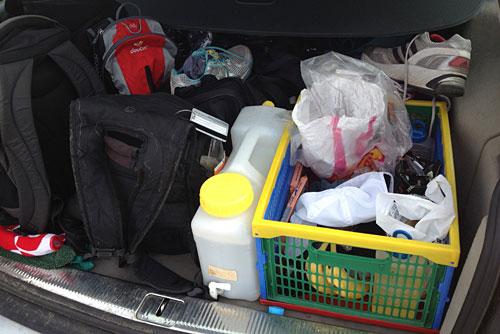 Kofferraum mit Laufschuhen, Rucksäcken und Verpflegung