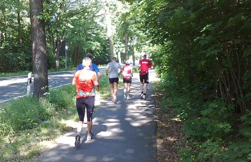 Läuferinnen und Läufer auf schattigem Radweg