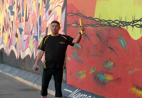 Läufer mit Staffelstab an der Berliner East Side Gallery