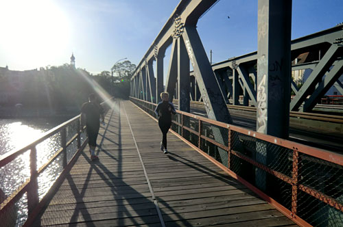 Läuferin und Läufer auf Brücke
