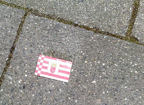Werbekarte mit Speckflaggen-Rückseite auf Fußweg in Bremen