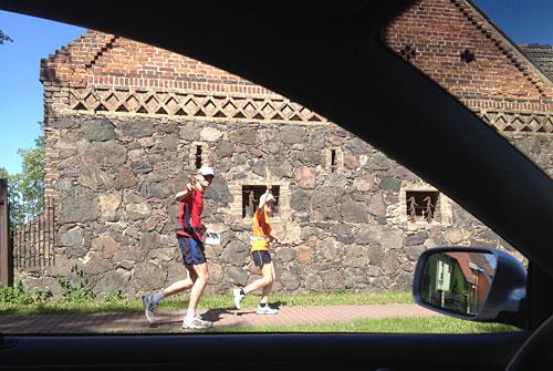 Läufer vor altem Haus